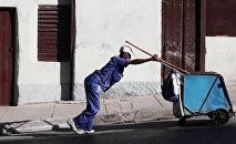 Мужчина толкает тележку для мусора