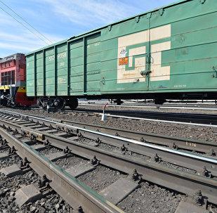Тепловоз с грузовыми вагонами на путях