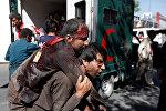 Афганский мужчина несет раненого в больницу после взрыва в Кабуле, Афганистан