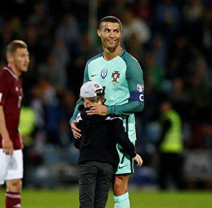 Криштиану Роналду обнимает мальчика, который выбежал на поле во время футбольного матча Португалия - Латвия