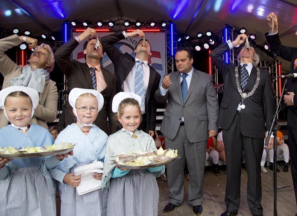 Голландский министр финансов Ян Кеес де Ягер и мэр Гааги Йозиас Ван Аартсен кушают селедку во время праздника День селедки в Схевенингене