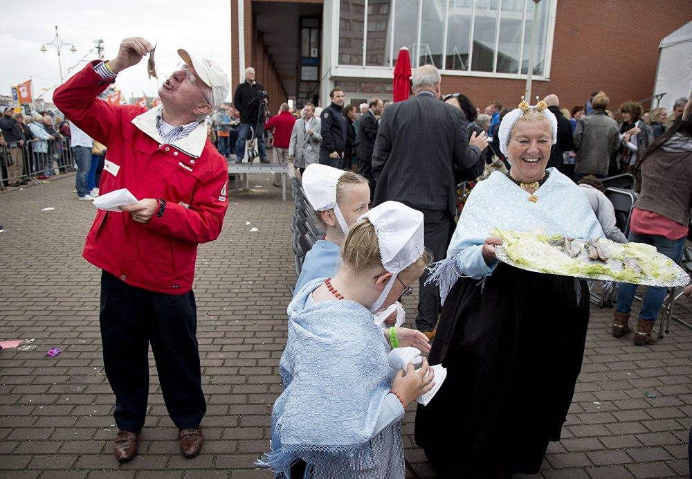 Женщина в национальном костюме угощает селедкой в День селедки в городе Схевенингене