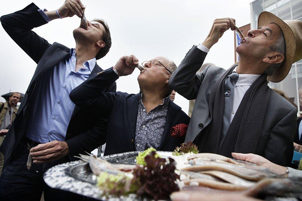 Голландский политик Народная партия за свободу и демократию Марк Рютте (слева), знаменитый повар Брахекке (C) и голландский министр образования, культуры и науки Рональд Пластерк наслаждаются маринованной сельдью