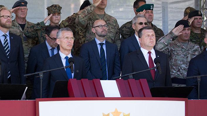 Генсек НАТО Йенс Столтенберг и президент Латвии Раймондс Вейонис (на первом плане) на церемонии развертывания многонационального батальона НАТО в Латвии