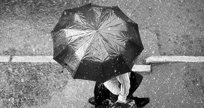 Человек с зонтиком под дождем