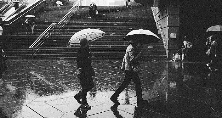 Cilvēki ar lietussargiem