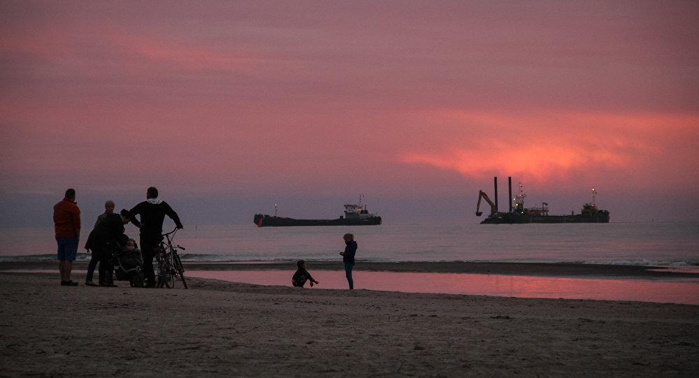 Закат на пляже в Павилосте, на фоне - рыбацкие суда и отдыхающие