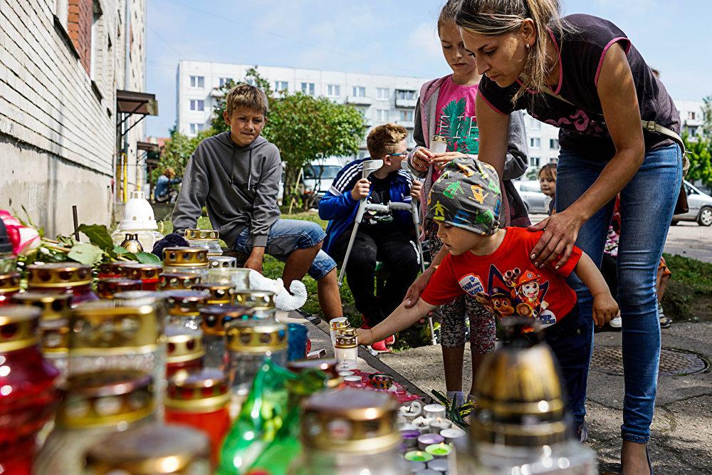 Pieaugušie un bērni nes ziedus, sveces un rotaļlietas mazā Vaņas piemiņai