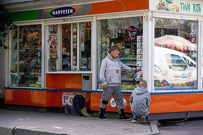 Дети ищут мелочь у киоска в Лиепаи