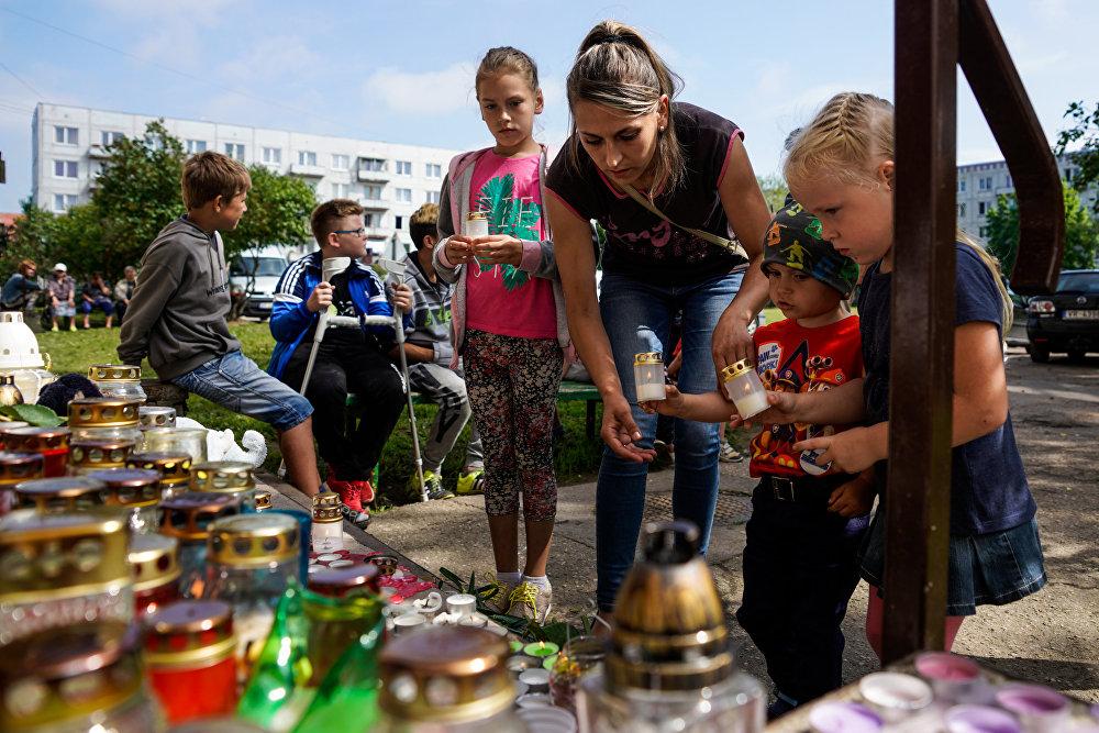 Liepājas iedzīvotāji noliek ziedus un rotaļlietas pie Vaņas kāpņu telpas durvīm