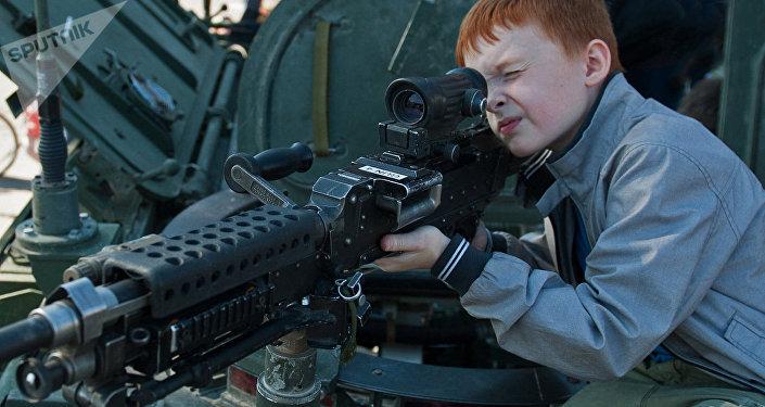 Мальчик осматривает пулемет