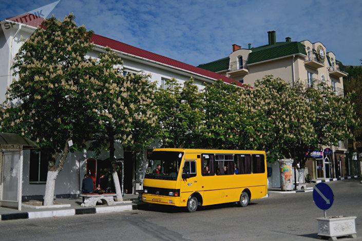 Автобус под цветущими каштанами на одной из улиц Балаклавы