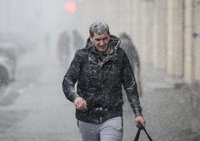 Прохожий на улице во время снегопада