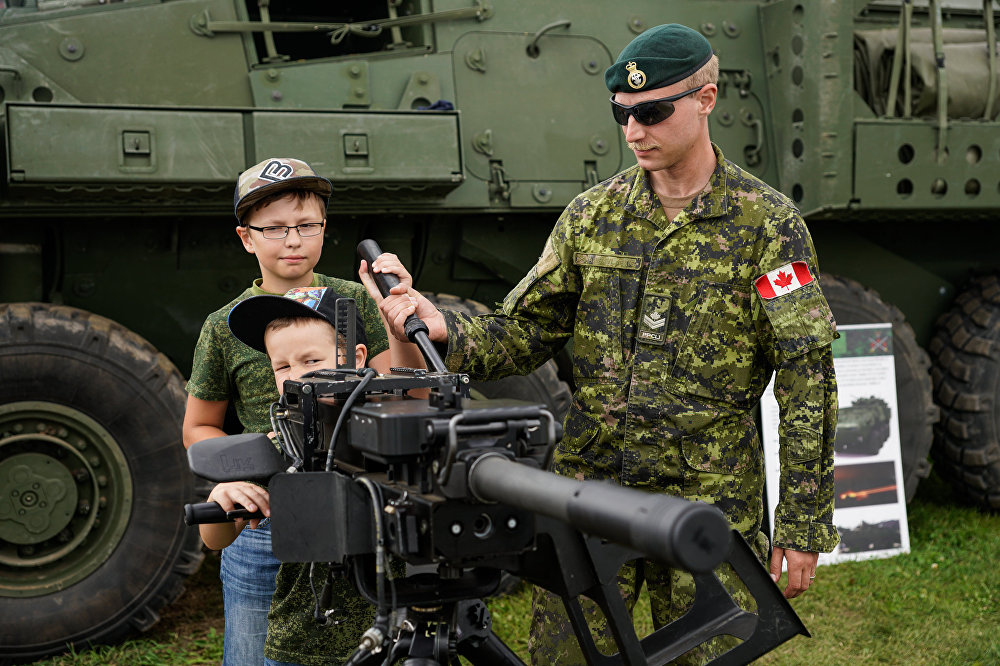 Kanādas karavīrs demonstrē bērniem automātisko granātmetēju