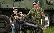 Военнослужащий Канады демонстрирует детям автоматический гранатомёт