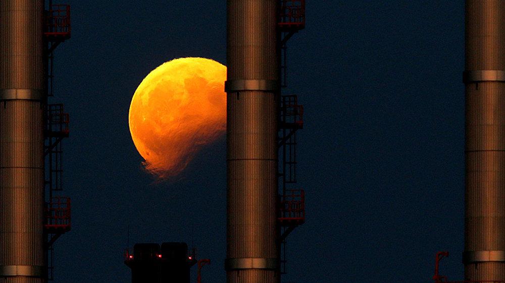 Восходящая луна  во время частичного лунного затмения за трубами электростанции в Делимаре, недалеко от Мальты
