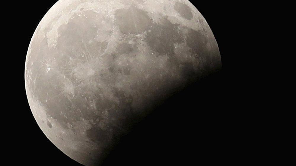 Луна во время частичного лунного затмения в небе Каира