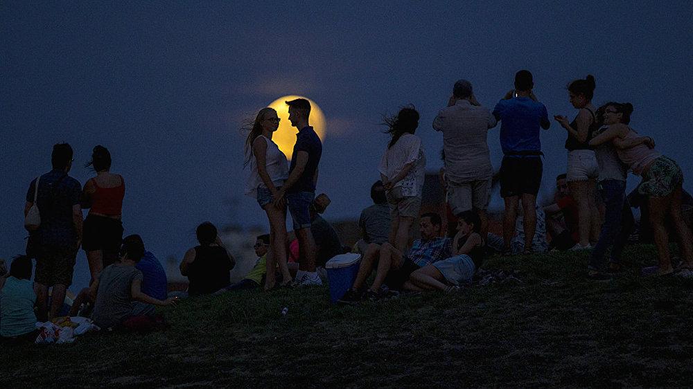 Люди наблюдают за восходящей луной во время частичного лунного затмения на вершине холма в парке Тио Пио в Мадриде