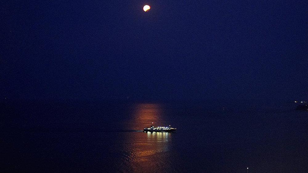 Луна, наблюдаемая в частичном лунном затмении над кораблем на острове Закинтос
