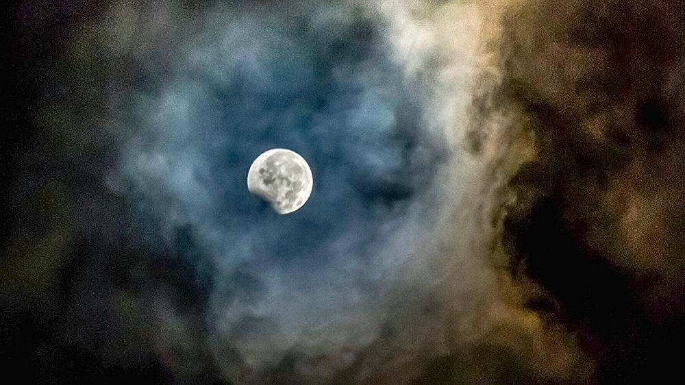 Луна, обрамленная пеплом от вулкана Маунт Синабунг, видна во время частичного лунного затмения в провинции Северная Суматра в Индонезии