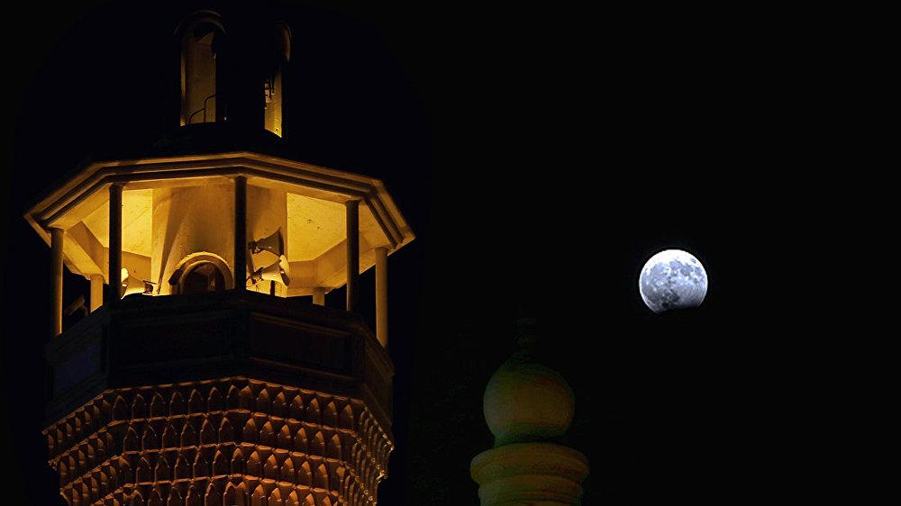 Луна во время частичного лунного затмения в небе Кувейта