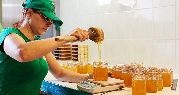 Готовый мед заботливые руки аккуратно разливают по баночкам
