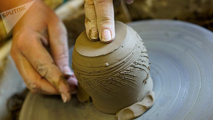 Под умелыми руками на гончарном круге рождается будущий горшочек