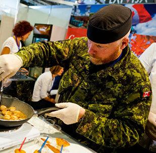 Канадский военный из сводного батальона НАТО в Латвии готовит гребешки