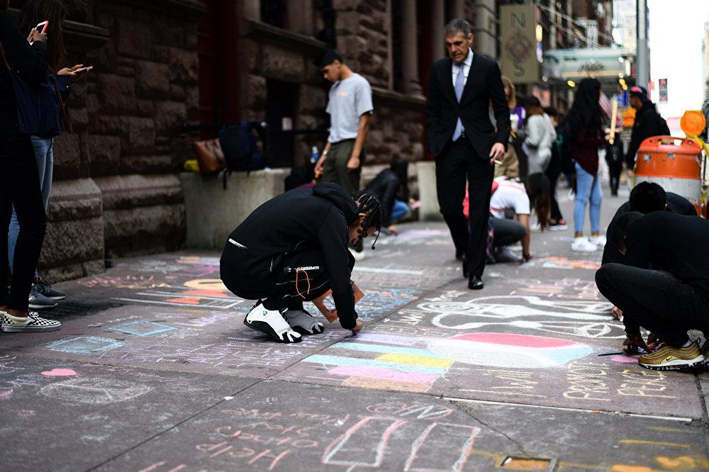 Учащиеся рисуют башни-близнецы и пишут сообщения на тротуаре перед своей школой 11 сентября 2017 года в Нью-Йорке в связи с 16-й годовщиной терактов