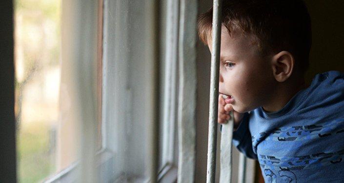 Воспитанник детского дома смотрит в окно