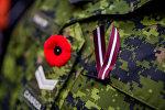 Красный мак - символ жертв всех военных и гражданских вооруженных конфликтов и латвийская ленточка на форме канадского военнослужащего