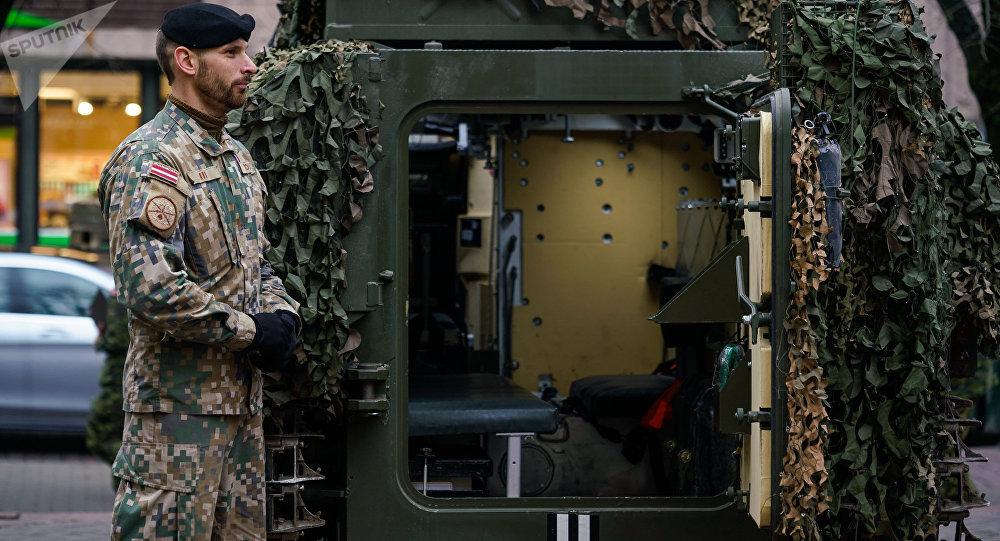 Латвийский военный у латвийского бронетранспортера CVRT