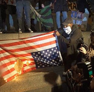 Anonymous aktīvisti sadedzināja ASV karogu protesta akcijas laikā Londonā