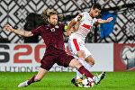 Латвийский футболист Каспарс Горкшс (слева)