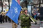 Военнослужащий Канады несет флаг НАТО на военном параде в Риге