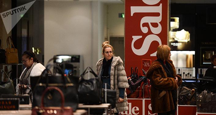 Женщина выбирает сумку во время зимней распродажи