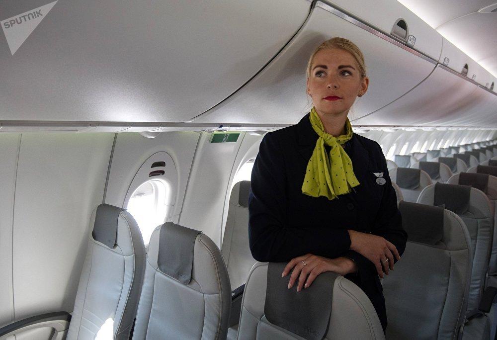 Стюардесса в салоне самолета Bombardier CS300 латвийской авиакомпании airBaltic