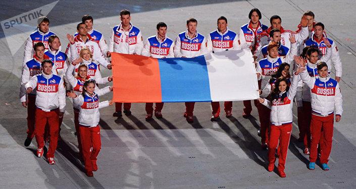 Krievijas izlases atlēti ar valsts karogu XXII ziemas Olimpisko spēļu slēgšanas ceremonijā