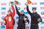 Скелетонист Мартинс Дукурс (в центре) выиграл этап Кубка мира в Инсбруке, вторым стал южнокреец Ян Сунбин (слева), третьим - россиянин Никита Трегубов (справа)