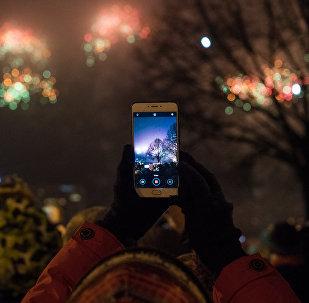 Женщина снимает на телефон новогодний салют