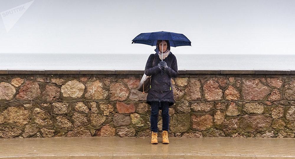 Девушка под зонтом на улице Юра, станция Дзинтари