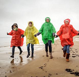 Девушки в дождевиках на пляже Юрмалы