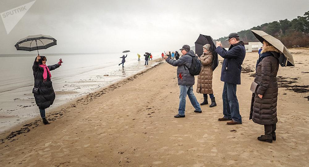 Туристы фотографируются на пляже Юрмалы