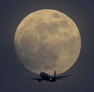 Самолет на фоне полной луны в небе над Лондоном, Великобритания