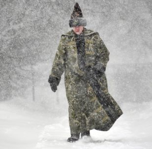 Молодой человек в историческом костюме во время снегопада на территории музея-заповедника Коломенское