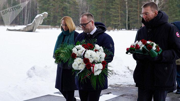 Министр культуры Даце Мелбарде, министр иностранных дел Эдгарс Ринкевичс и председатель Саласпилсской думы возлагают цветы на мемориале в Саласпилсе
