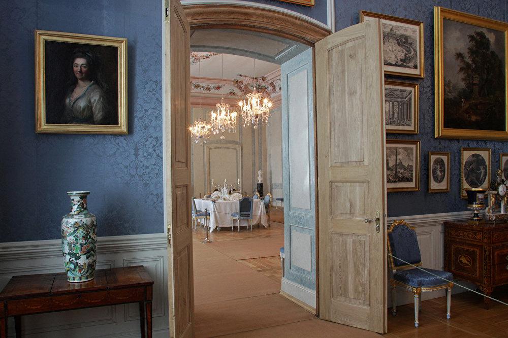 Filmā: mūzikas salons Rostovu namā Pēterburgā. Muzejā: salons ar holandiešu meistaru gleznām, durvīs redzama hercoga ēdamzāle