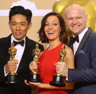 Kacuhiro Cudzi, Lūsija Sibika un Deivids Maļinovskis ar Oskara statuetēm par labāko grimu un frizūrām filmā Tumšie laiki.