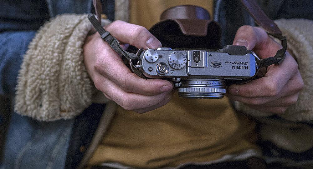 Fotokamera fotogrāfa rokās