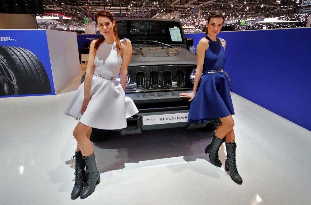 Модели у автомобиля Black Hawk у стенда компании Chelsea Truck Company на автосалоне Geneva International Motor Show 2018 в Женеве, Швейцария